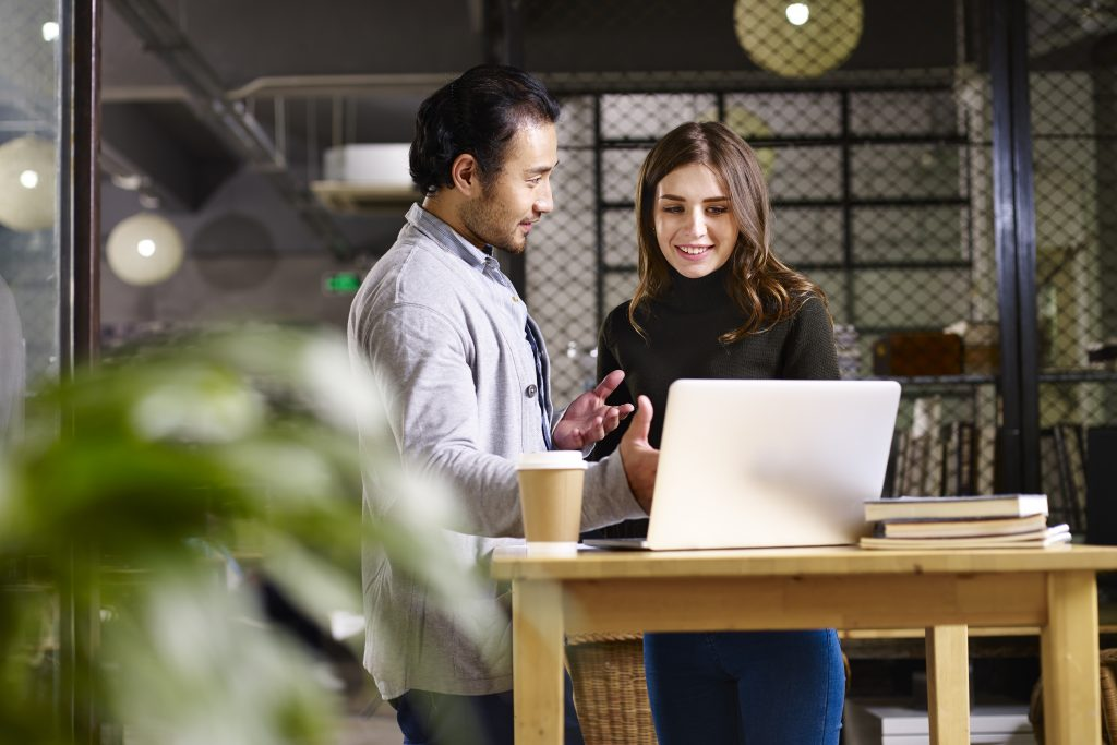 group of two young beautiful male and female business colleagues share files fast and easily on laptop